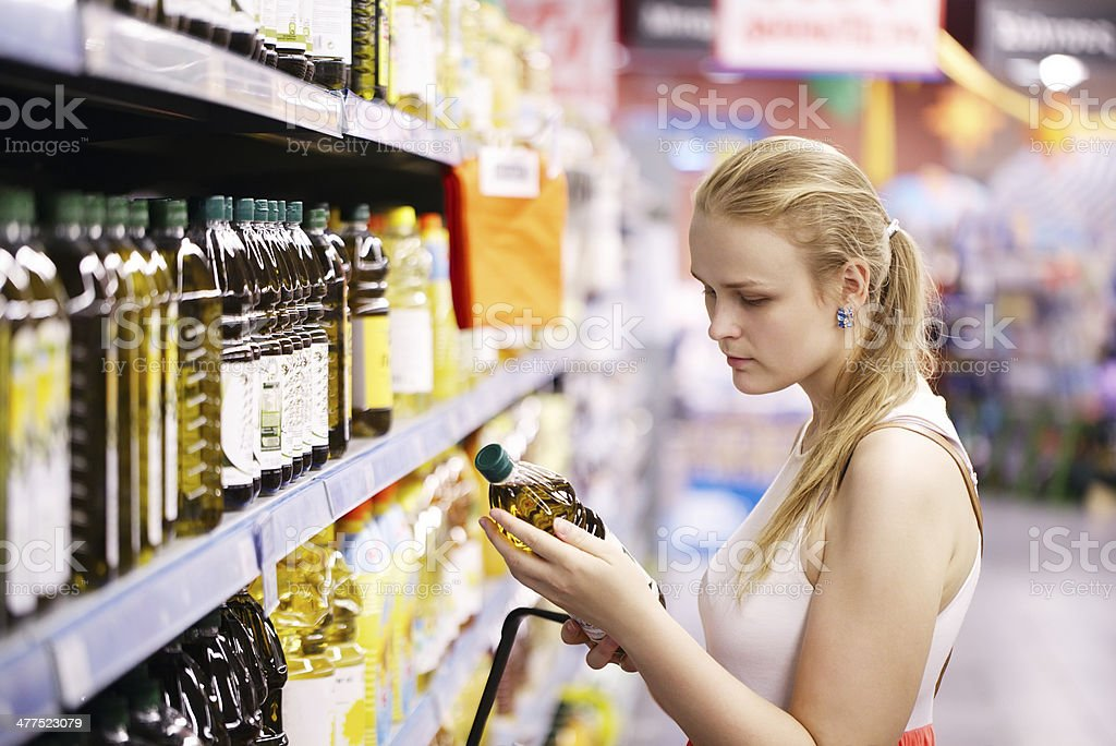 Young woman buying olive oil stock photo