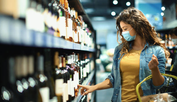 Young woman buying some wine at a supermarket during coronavirus pandemic stock photo