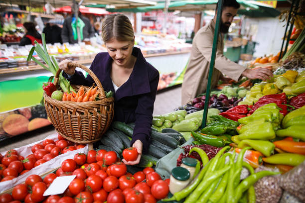 Young woman buying vegetables at farmer's market stall. stock photo
