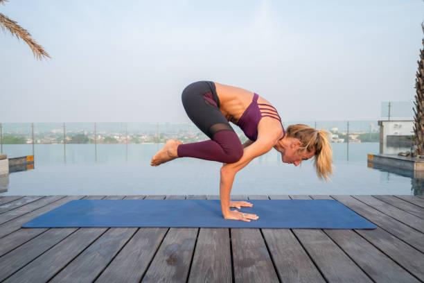 Junge Frau durch einen Infinity-Pool, die Ausübung von Yoga-Krähe-Pose auf Yoga-Matte in Agra, Indien – Foto