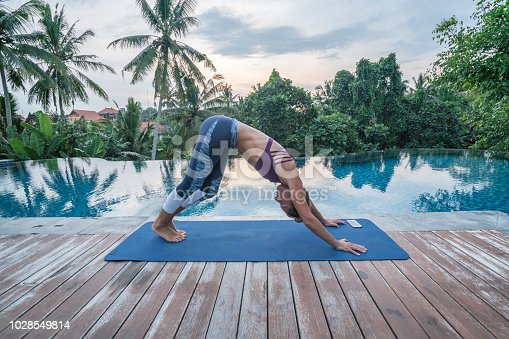 istock Young woman by an infinity pool exercising yoga on yoga mat using mobile app on smart phone, Ubud, Bali 1028549814