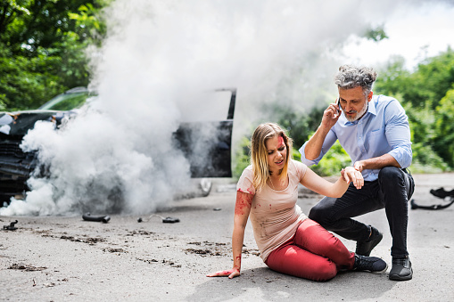 istock Young woman by the car after an accident and a man making a phone call. 1047076626