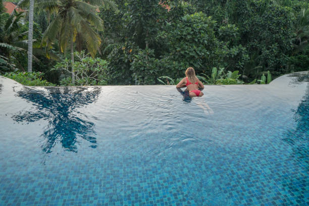 young woman by the edge of an infinity pool, ubud, bali enjoying tropical climate vacations in asia - mulher natureza flores e piscina imagens e fotografias de stock