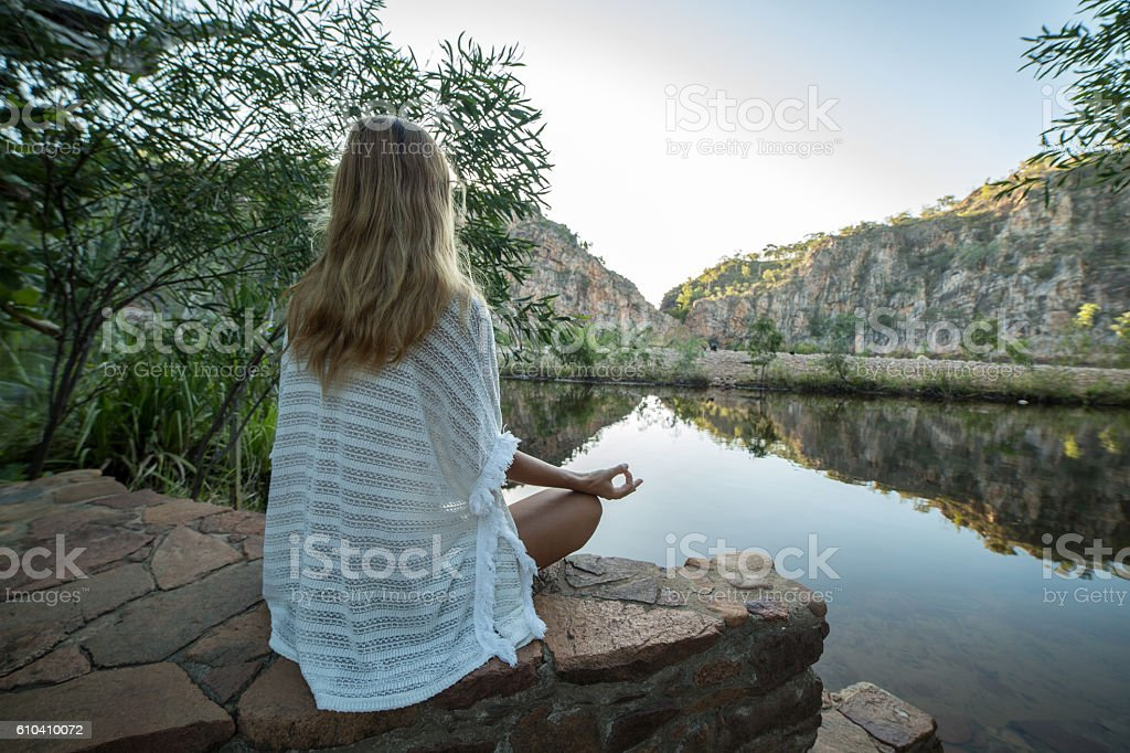 Young woman by the lake exercises yoga in lotus position stock photo