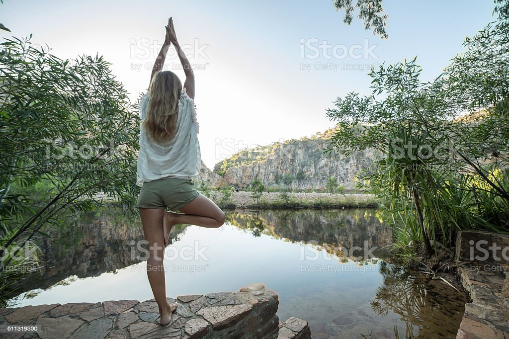 Young woman by the lake exercises yoga in tree pose stock photo