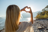 Young woman by the lake making a heart shape with her hands. Lake and mountain landscape, Swiss Alps on the background.