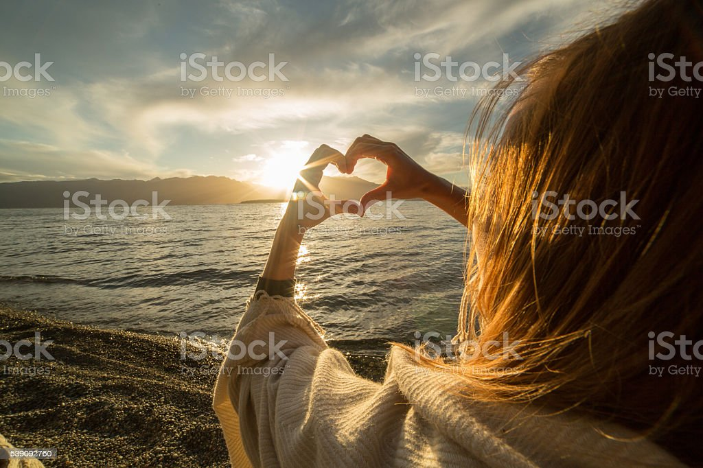 Young woman by the lake making heart shape finger frame stock photo