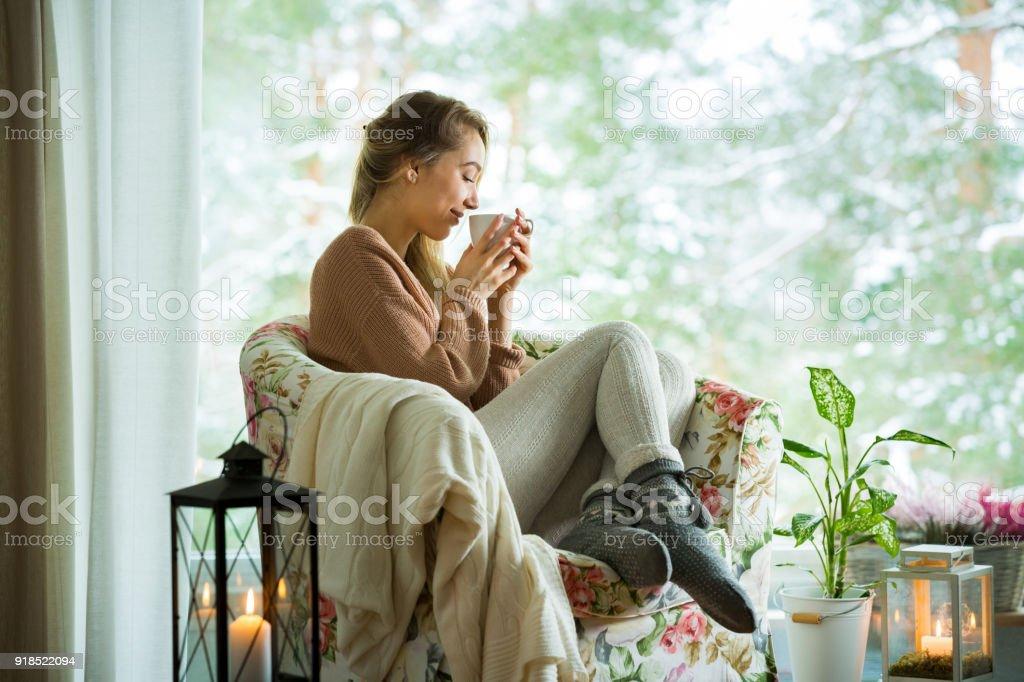 Jovem mulher pela janela com uma xícara de café quente - foto de acervo