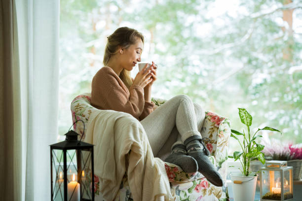 young woman by the window with cup of hot coffee - aura stock photos and pictures
