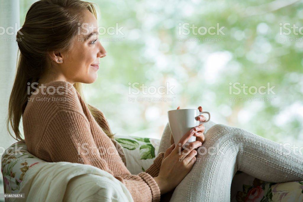 Young woman by the window with cup of hot coffee stock photo