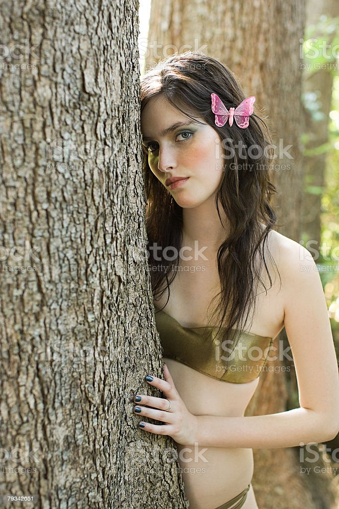 Young woman by tree stock photo