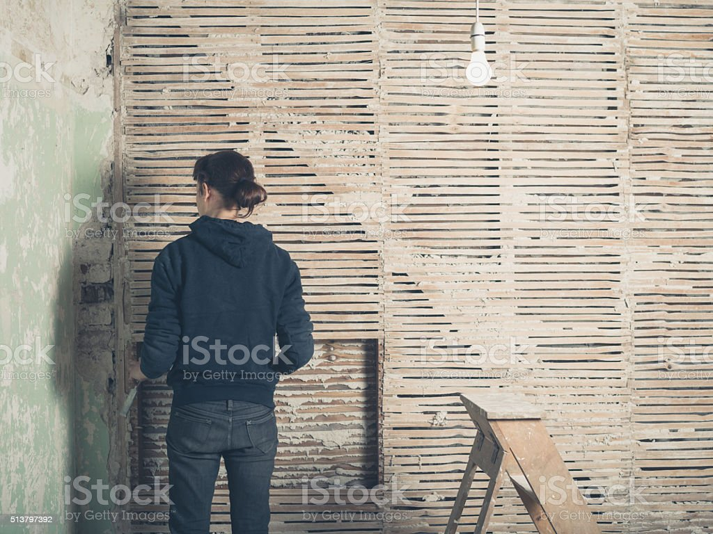 Young woman by wattle and daub wall stock photo