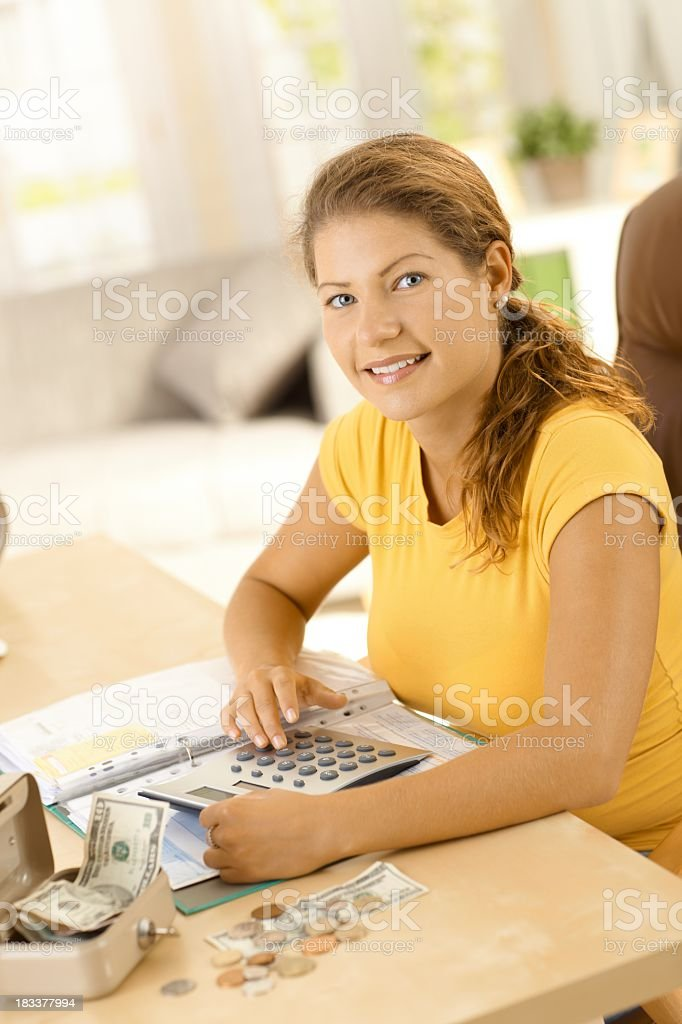 Happy young woman sitting in living room at home, using calculator to...