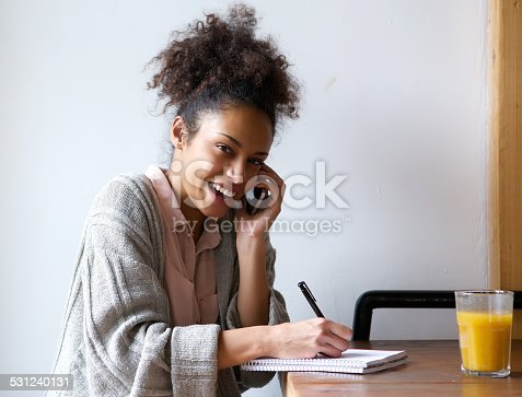 istock Young woman calling by phone and writing in notebook 531240131