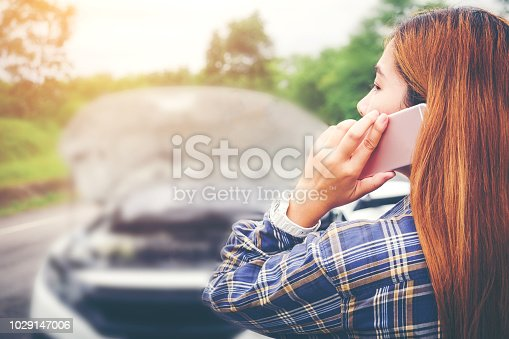 istock Young Woman calling for assistance with his car broken down by the roadside 1029147006