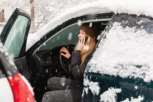 istock Young woman calling for help or assistance inside snow covered car. Engine start in frost. Breakdown services in the winter 1182598195