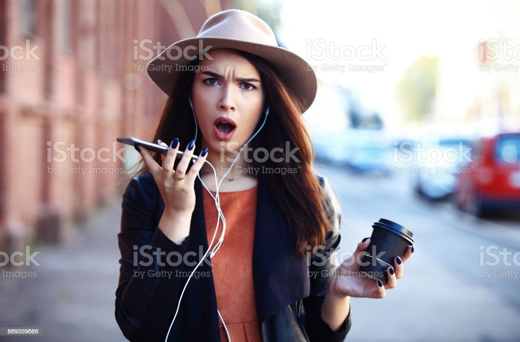 Young woman calling phone with hands free and laughing - outdoor in street stock photo