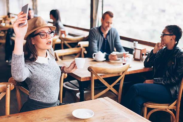 young woman calling the waiter at coffee shop - brille bestellen stock-fotos und bilder
