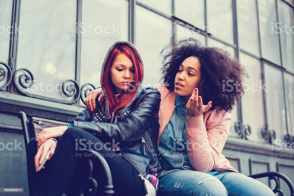 Young woman calming a depressed friend stock photo
