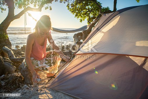 istock young woman camping on the beach preparing tent at sunset 1191599307