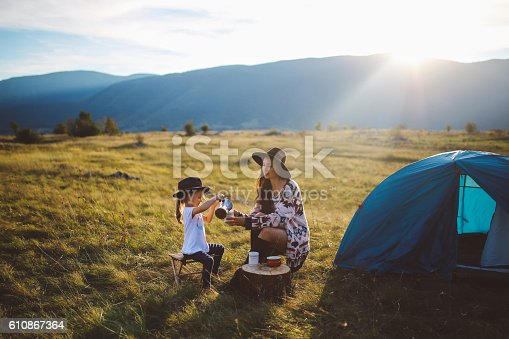 Landscape in Dinaric Alps, mountain range in Southern Europe, on the border of Croatia and Bosnia. Young brunette woman is camping with her baby girl child. They are sitting in the in front of a small tent, enjoying a beautiful view over the valley under the mountains, watching the horizon as the sun sets, playing games and having fun in the nature outdoors. They're dressed in fashionable hippie clothes, enjoying freedom in the nature, wearing hats and having a coffee in a small stove top espresso pot.