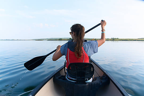 young woman canoeing in the lake on a summer day. - カヤッキング ストックフォトと画像