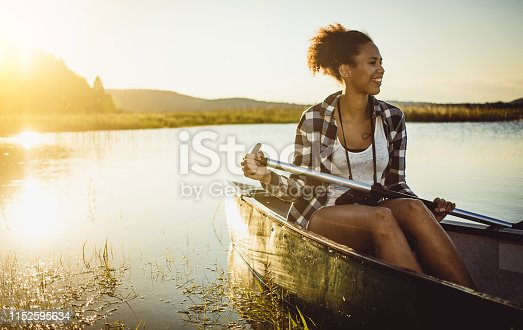 Young Woman Canoeing on The Lake