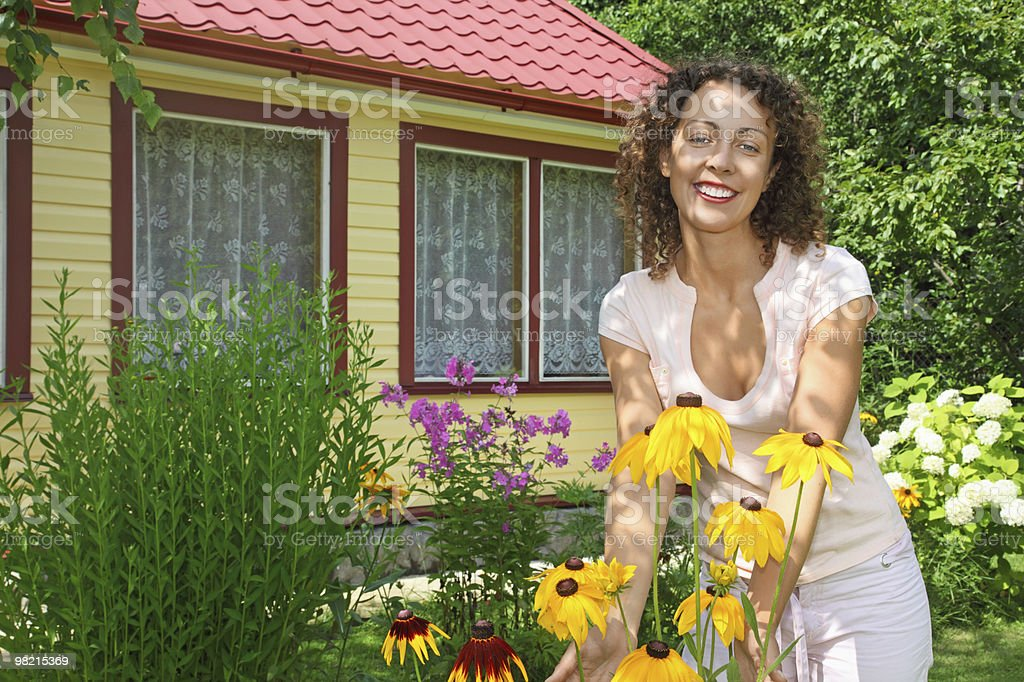 Young woman care of flowers in garden near house royalty-free stock photo