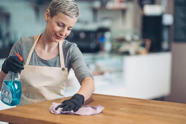 Junge Frau sorgfältig reinigen einen Tisch mit einem Desaimisierungsspray – Foto