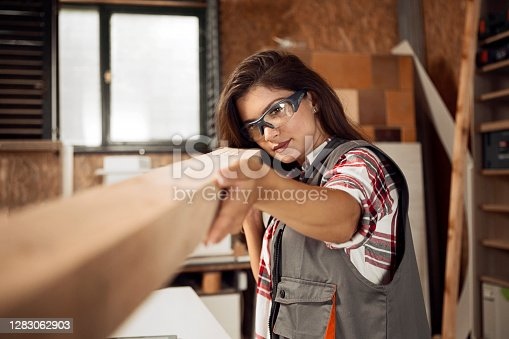 Female Carpenter carrying Wooden Plank smiling