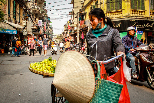 A young woman carries a plate of fruit on her bicycle in the old quarter of Hanoi in northern Vietnam