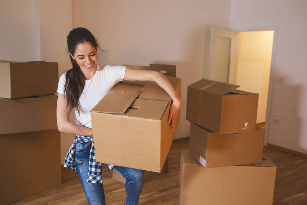 Young woman carrying big cardboard full of home essentials into a new home. stock photo
