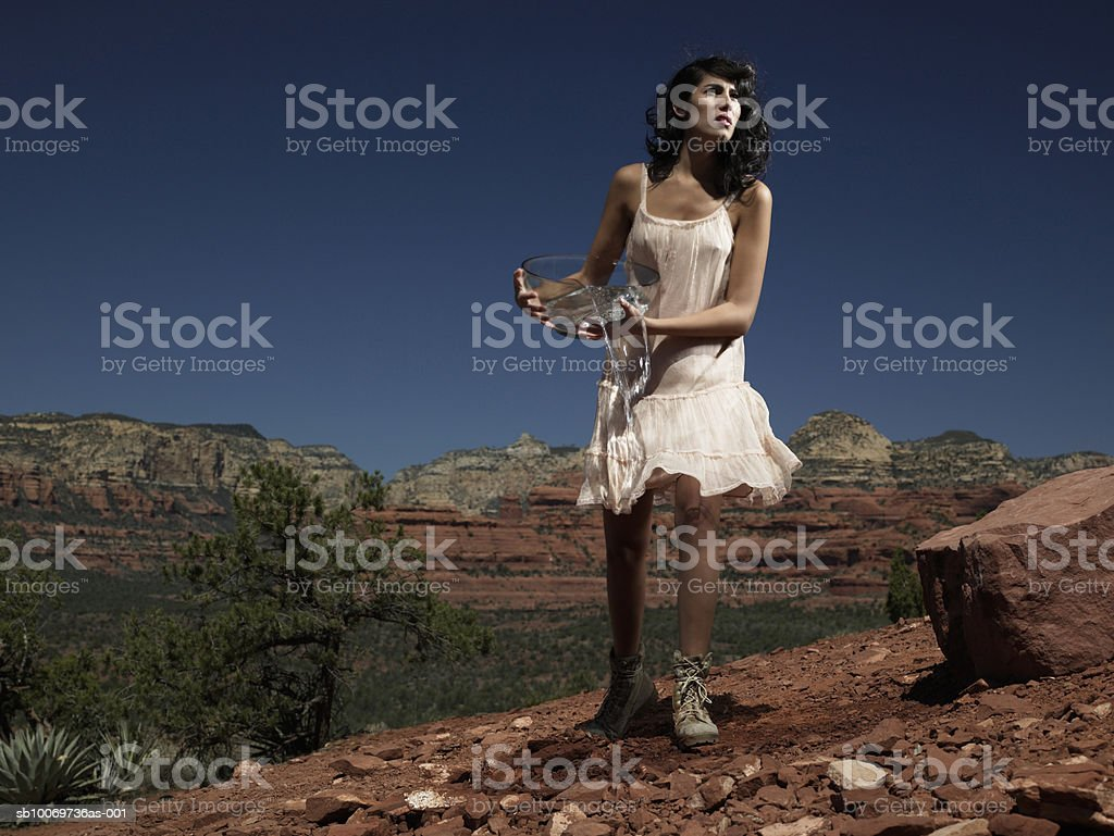 Young woman carrying bowl of water, low angle view royalty free stockfoto