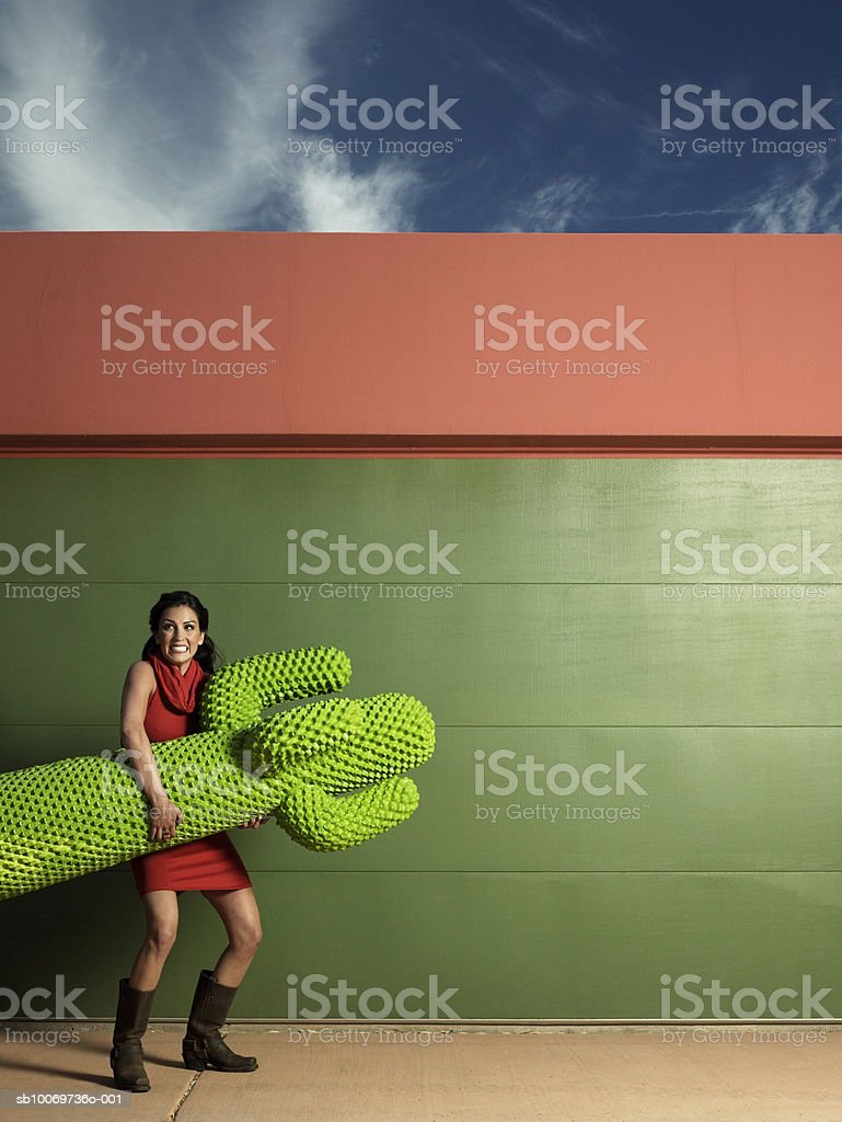 Young woman carrying fake cactus royalty-free stock photo