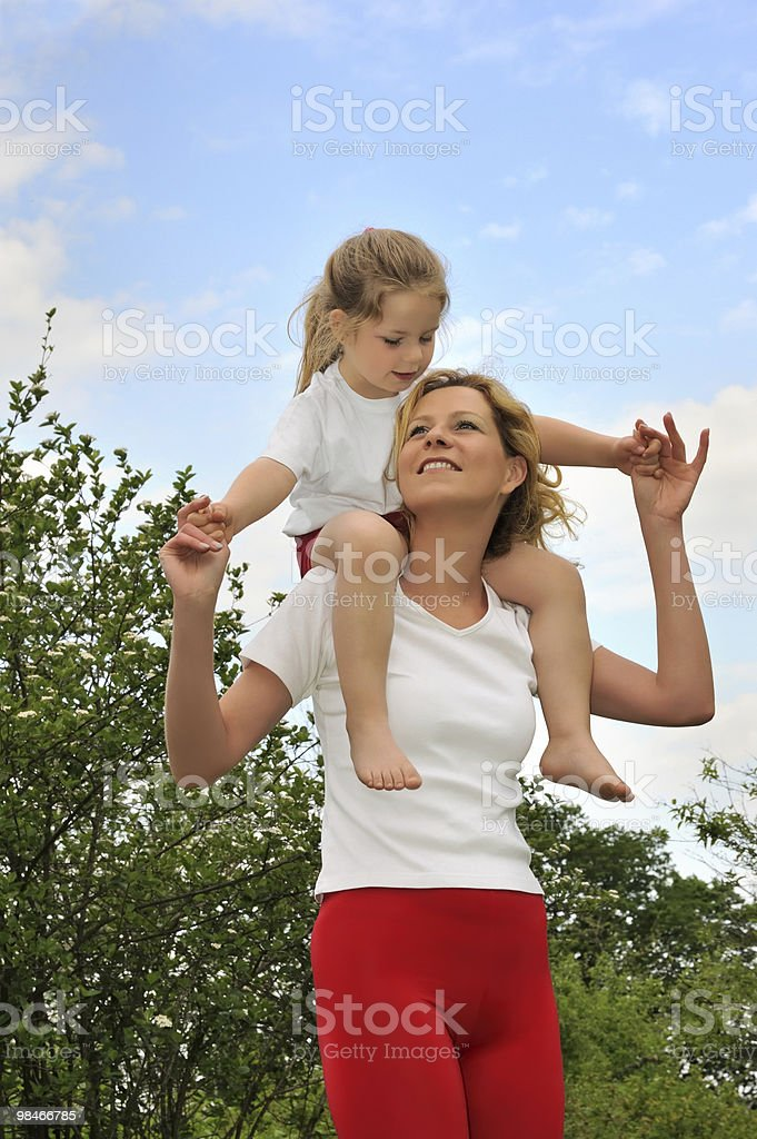 Young woman carrying her daughter over the shoulders royalty-free stock photo