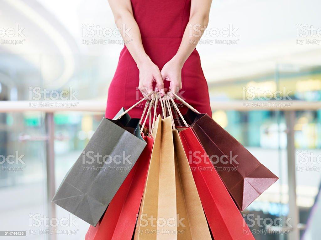 young woman carrying paper shopping bags in modern mall - foto de stock