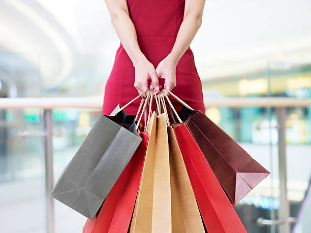 young woman carrying paper shopping bags in modern mall stock photo