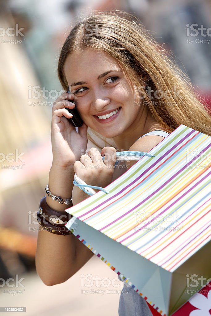 Young woman carrying shopping bags and talking on mobile phone royalty-free stock photo