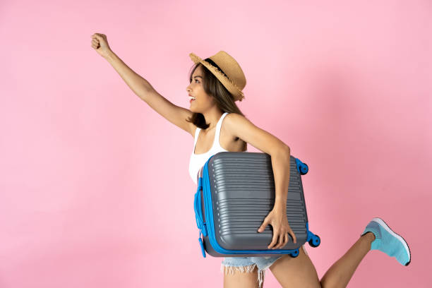 Young woman carrying suitcase with arm raised against pink background