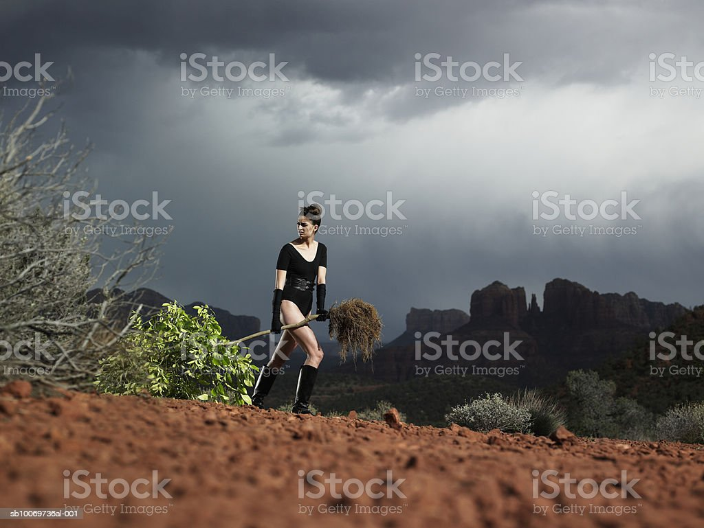 Young woman carrying uprooted tree at dusk 免版稅 stock photo