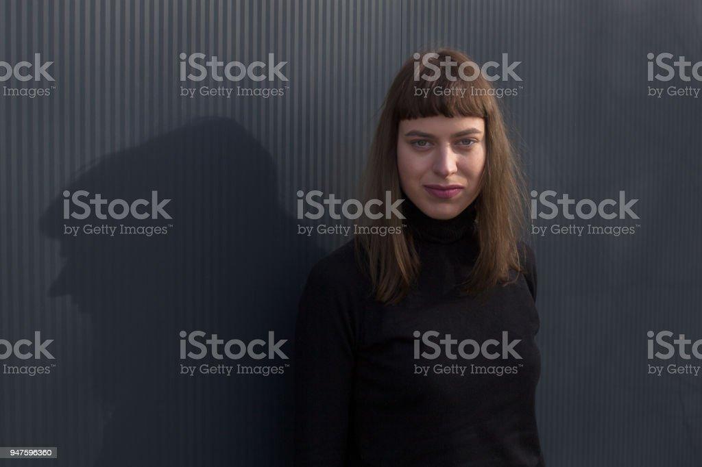 junge Frau wirft einen Schatten auf schwarzen Kunststoff-Hintergrund – Foto