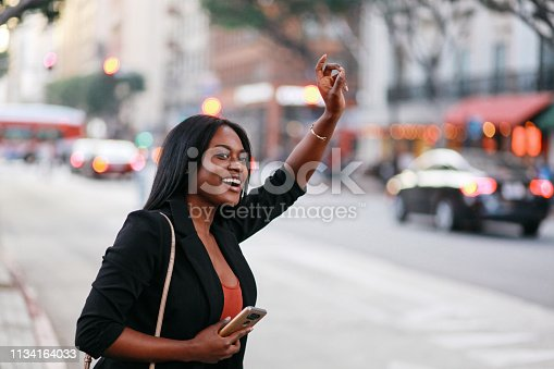 Young, fashionably dressed mixed race Latina woman on the streets of downtown Los Angeles, trying to catch a cab after work.