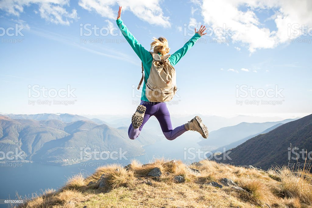Young hiking woman at the top of a mountain jumping high up for...