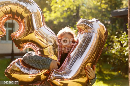 Cheerful woman celebrates a thirty one years birthday with big golden balloons