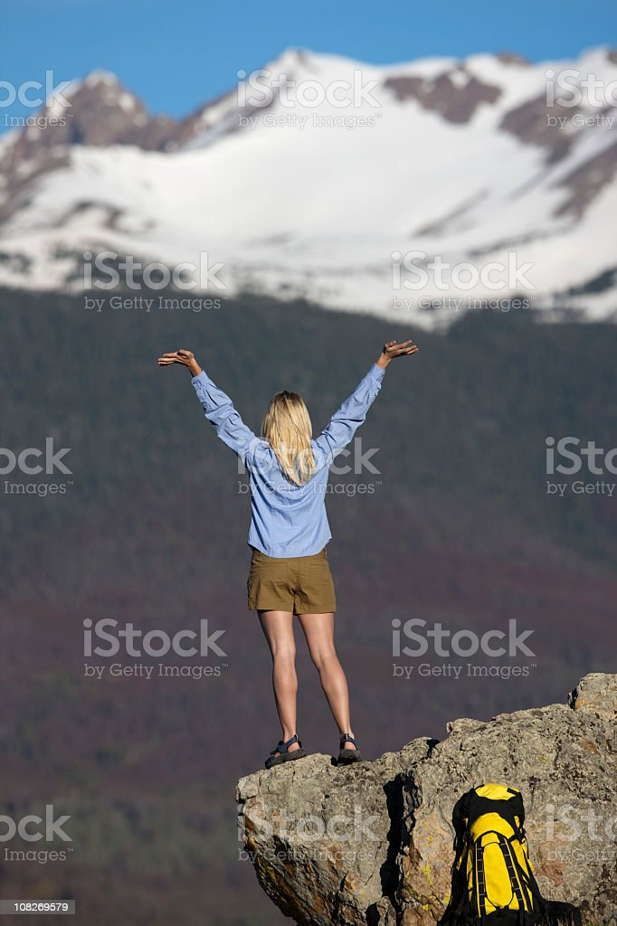 Young Woman Celebrating After Backpacking To Top Of Mountain royalty-free stock photo