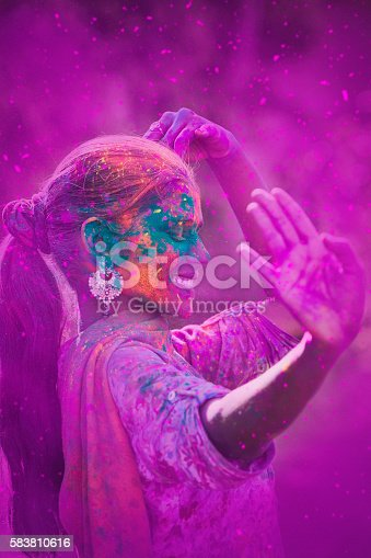 Young woman covered in colored dye celebrating Holi festival in Jaipur, India.