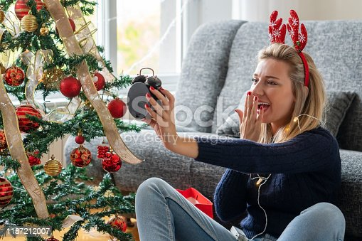 istock Young woman celebrating holidays at home 1187212007