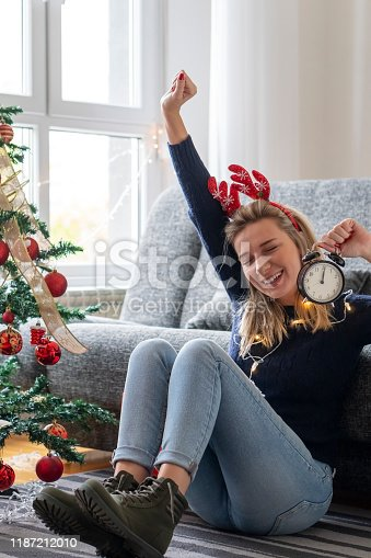 istock Young woman celebrating holidays at home 1187212010