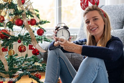 istock Young woman celebrating holidays at home 1187212011