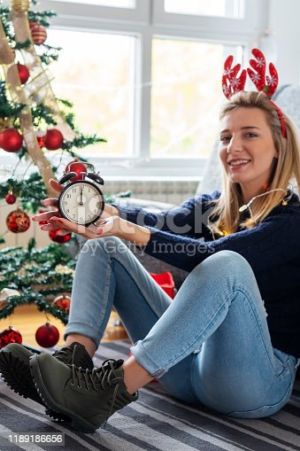 istock Young woman celebrating holidays at home 1189186656